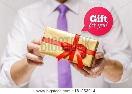 Male hands holding a gift box. Present wrapped with ribbon and bow. Gift for you speech bubble. Man in white shirt and necktie.