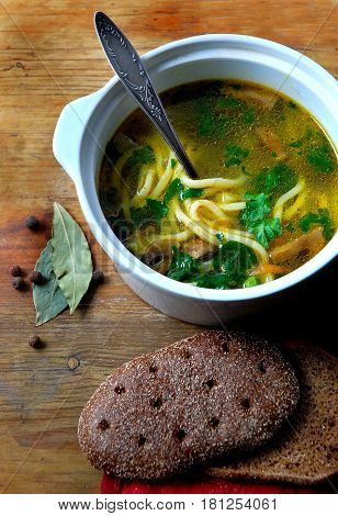 photos of lunch, mushroom soup with noodles, spices, bread. Beautiful photo of the soup. Chicken soup with mushrooms, noodles and greens.