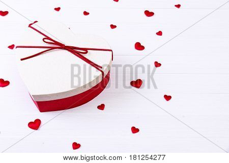 Gift box with hearts. Heart-shaped present wrapped with ribbon and bow. Valentines day love package. On white wooden table.