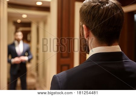 Close up shot of back of bearded man wearing suit and looking at himself in mirror in wood dressing room