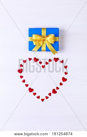 Gift box with red heart. Present wrapped with yellow ribbon. Christmas or birthday blue package. On white wooden table.