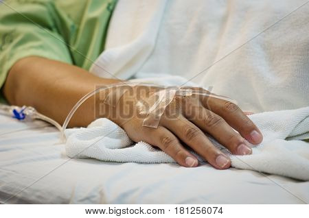 Hand of Male patient lying on a hospital bed receiving saline.