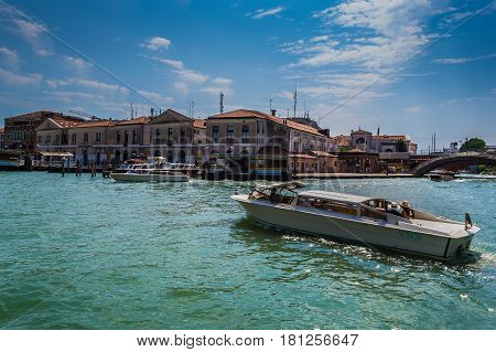 Venetian water taxi - Venice Italy - 04 August 2016: Water cabs passing by Vaporetto departing from the station in the background.