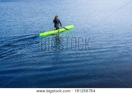 Young sport woman paddling with green canoe on the blue river on a sunny day. Young women canoeing. Kayak. Girl kayaking in the river Dnieper. Activities on the water. The concept of a way of life. The concept of overcoming obstacles.