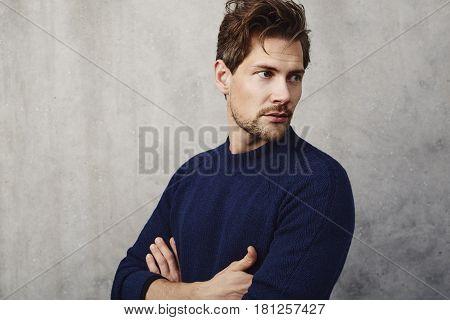 Handsome guy in blue sweater looking away