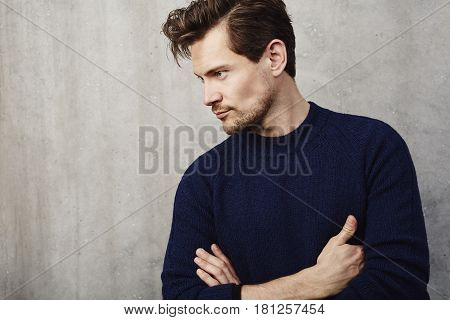 Handsome man in blue sweater looking away