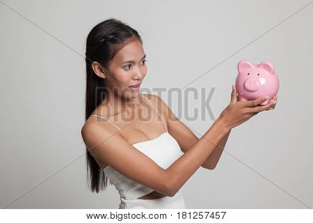 Young Asian Woman With A Pig Coin Bank.