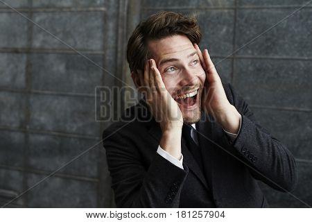 Mad Ecstatic businessman looking away studio shot