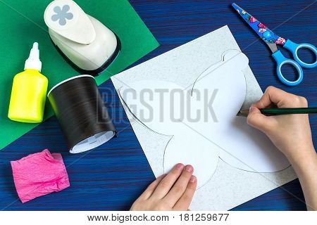 Making gift for Mother's Day by the child. Colorful bouquet of flowers out of paper. Children's art project. DIY concept. Step-by-step photo instruction. Step 2. Child draws box using template