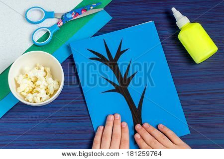 Making card by a child on spring theme. Blossoming tree on a blue background. Original children's art project. DIY concept. Step-by-step photo instruction. Step 4. Child glues a tree on card