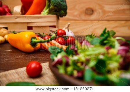 Sweet pepper, brocoli and cherry tomato. Mix salad leaves. Natural raw vegetables. Organic bio food on rustic wooden table.