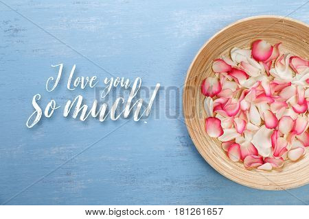 Petals of white and pink roses on blue painted rustic background. I love you so much. Fresh natural flowers in bowl. Dirty grunge wooden board.