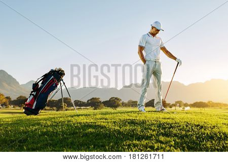 Full length of young man standing on golf course at sunset. Professional male golfer holding golf club on field.