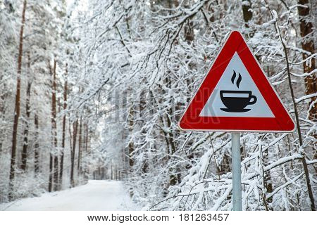 Snowy winter road. Hot coffee or tea icon. Attention sign. Forest with snow-covered trees. Beautiful wintertime.