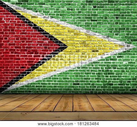 Guyana flag painted on brick wall with wooden floor