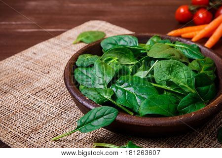 Spinach leaves in bowl. Carrot and cherry tomatoes. Raw fresh vegetable. Fresh natural plant leaf. Organic bio food on rustic wooden table.