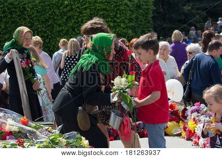 Kiev Ukraine - May 09 2016: Boy giving flowers to his grandmother - a veteran of the Second World War at the celebration of the anniversary of victory