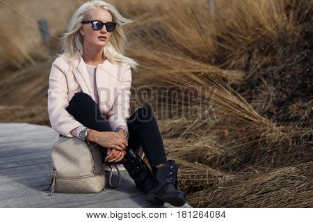 Effective blonde in sunglasses sits on wooden bridge
