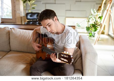 man on couch playing guitar on couch inventing new melody