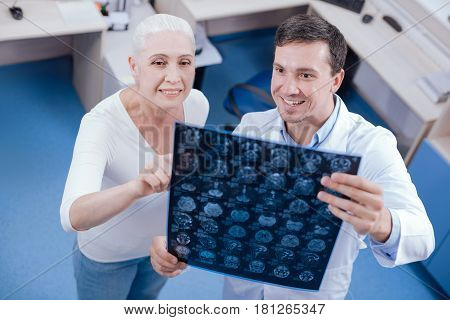 What does it mean. Happy positive senior woman pointing at the X ray and asking her doctor a question while visiting a hospital