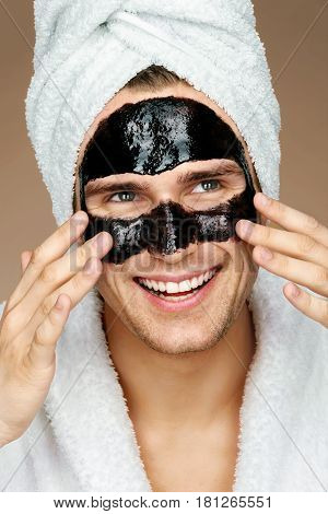 Happy man with black mask on the face. Photo of well groomed man receiving spa treatments. Beauty & Skin care concept