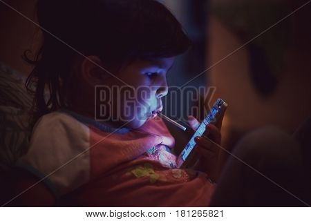 Small girl with lollipop watching a mobile phone.