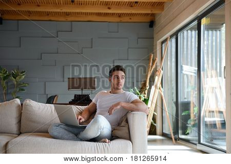 Young man looking away while working at laptop home