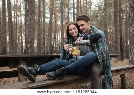 Smiling woman sitting near her young man pouring tea from thermos in wood
