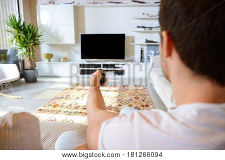Back view of man sitting on couch with remote controller against blank screen of TV