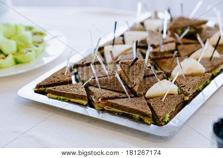 Delicious appetizer canapes of black bread on skewers, served on white plate