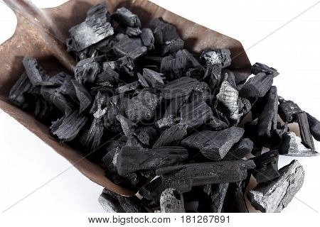 Pile of charcoal and shovel isolated on white