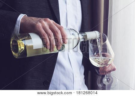 Horizontal close up of Caucasian man in black suit and white shirt pouring white wine into a tall glass from a bottle in a bar by the window natural lighting