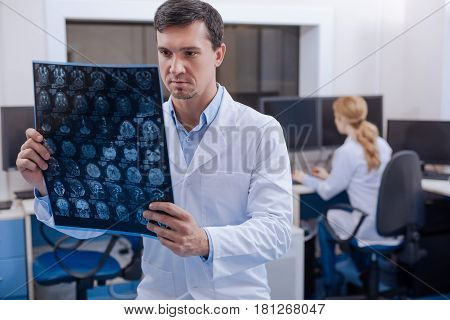 Oncological diagnosis. Handsome experienced nice doctor looking at an X ray image and putting a diagnosis while working in the oncology department poster