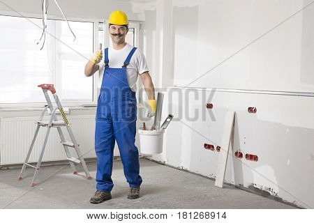 Construction worker wearing overalls and helmet making OK sign.