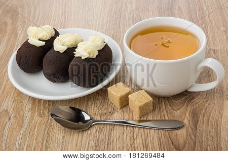 Chocolate Biscuit Cakes With Buttercream In Saucer, Tea, Sugar
