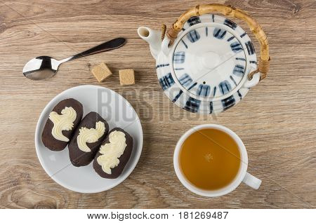 Chocolate Cakes With Buttercream In Saucer, Teapot, Tea, Sugar