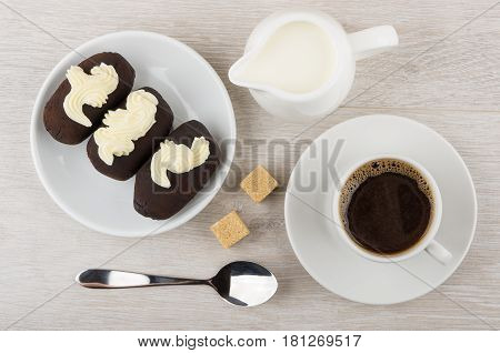 Chocolate Biscuit Cakes With Buttercream In Saucer, Jug Milk, Coffee