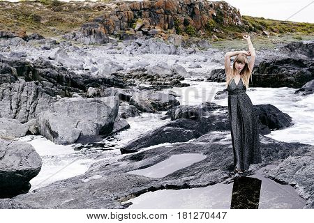 Sensuous woman in gray dress in rocky landscape