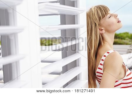 Sensuous young blond woman in swimwear against shutters