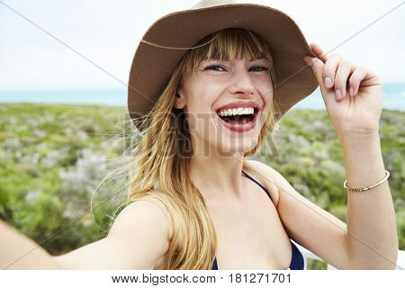 Laughing young woman adjusting hat for self portrait