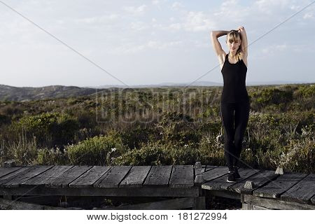 Young blond woman stretching outdoors on boardwalk