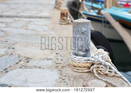 Wooden post with mooring ropes for tying boats and ships.