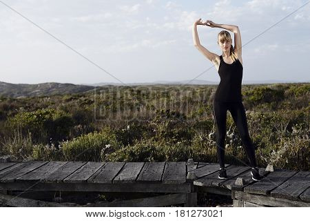 Athletic young blond woman stretching outdoors looking at camera