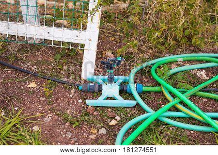 Garden hose pipe outdoor. Water taps and green garden hose with a sprayer