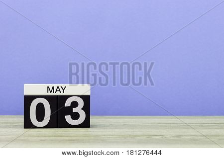 May 3rd. Day 3 of month, calendar on pink or purple background. Spring time, empty space for text.