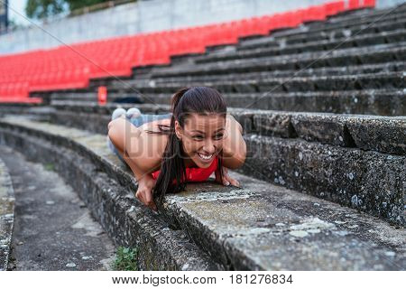 Attractive young woman doing push ups outdoors.