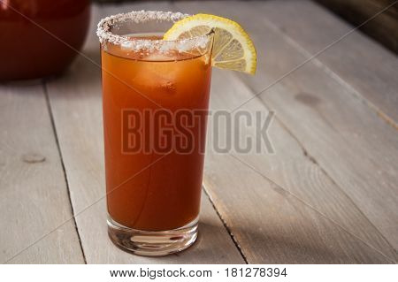 tomato juice with salt and lemon on wooden background
