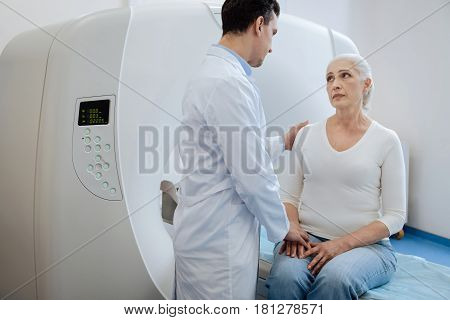 It must be difficult for you. Professional experienced male oncologist putting his hand on the patients shoulder and supporting her while telling her the diagnosis