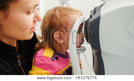 High tehnology in healthcare - optometrist in clinic checking little girl's vision - children's ophthalmology, horizontal