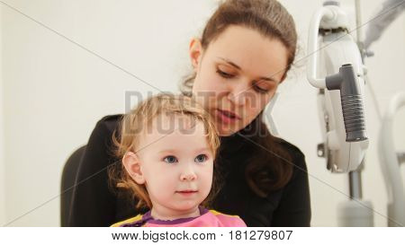 Children ophthalmology - mother and cute little girl - optometrist Checks Child's Eye, close up